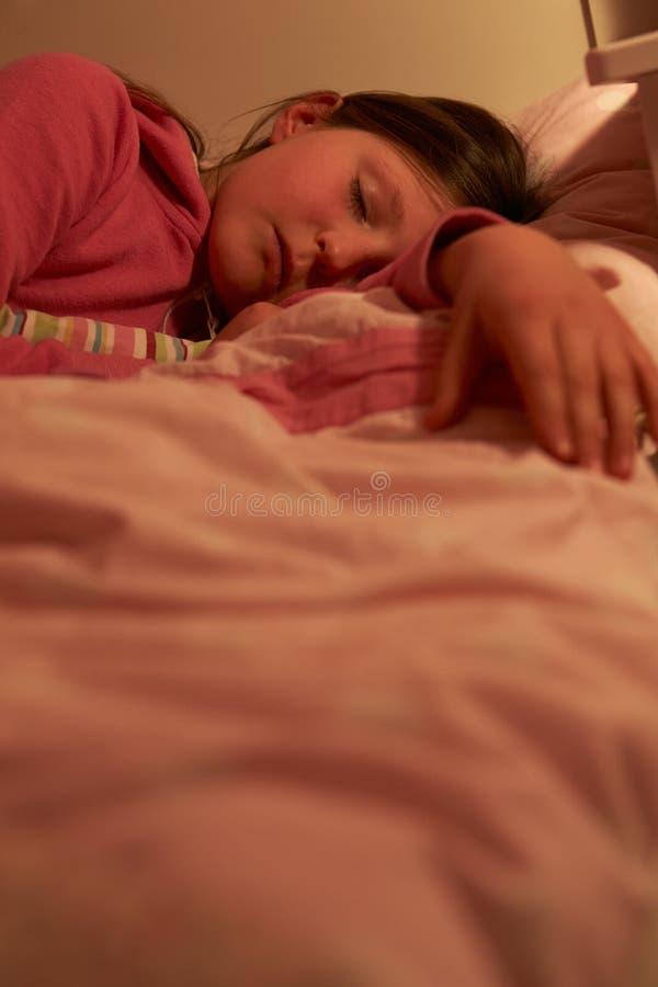 女孩睡着在床上在晚上 图库摄影