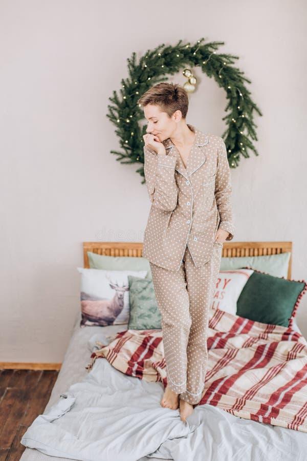 女孩睡衣卧室床圣诞节花圈 免版税库存图片