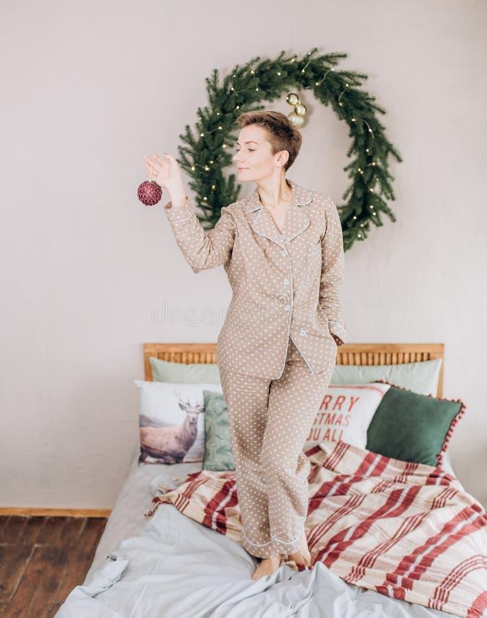 女孩睡衣卧室床圣诞节花圈 免版税库存照片
