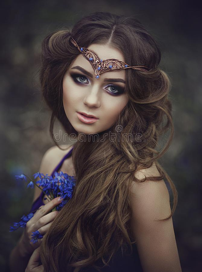 女孩矮子的画象与长的头发和蓝眼睛的,佩带与春天花花束的一个冠状头饰在森林女孩的 图库摄影