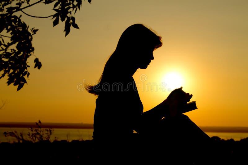 女孩祈祷的剪影 免版税库存图片