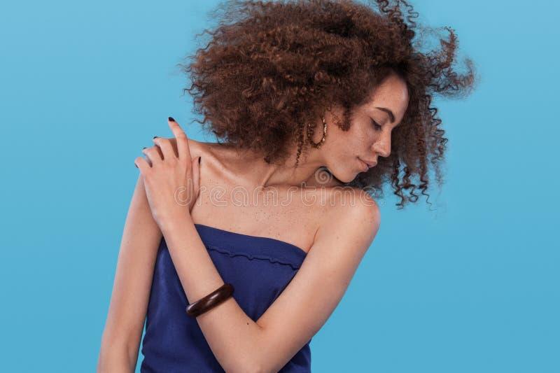 女孩秀丽画象有非洲的发型的 摆在蓝色背景的女孩 美丽的夫妇跳舞射击工作室妇女年轻人 免版税库存照片