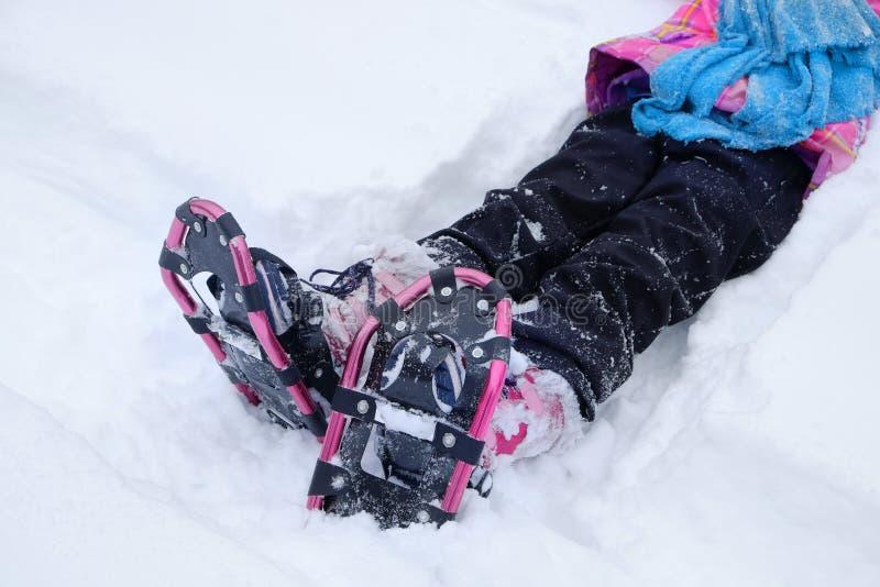 女孩穿上鞋子在冬天的Snowshoeing雪获得乐趣 免版税库存照片