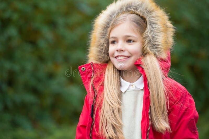 女孩穿戴毛茸的海角享用秋天自然公园 在舒适敞篷或海角上的皮 儿童白肤金发的长的头发走的温暖的夹克 库存图片