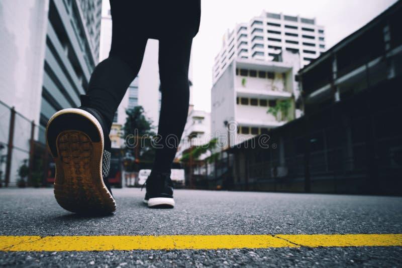 女孩穿黑跑鞋在公园跑 免版税库存照片