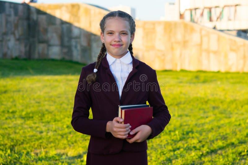 女孩站立与课本在日落和微笑 免版税库存照片