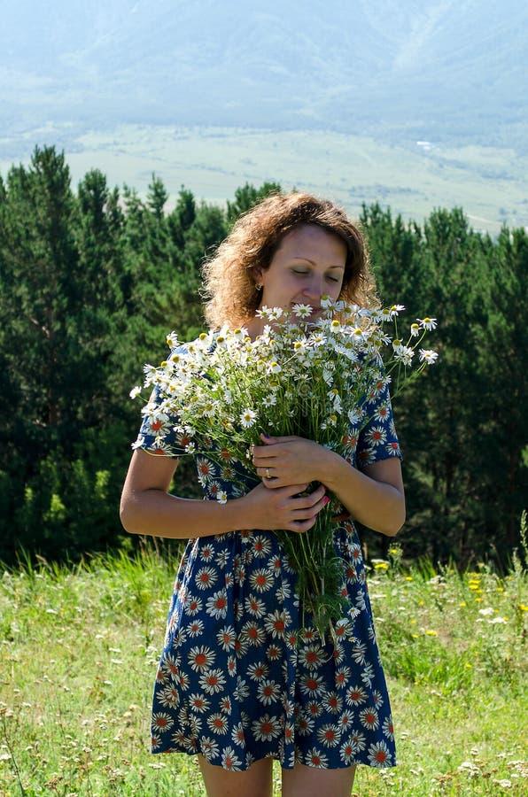 女孩站立与雏菊花束  免版税图库摄影
