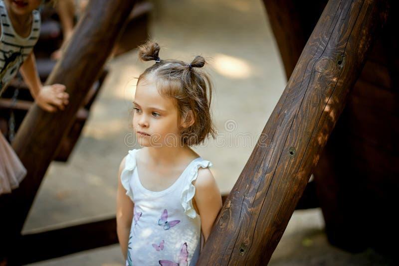 女孩站立单独在有沉思面孔的操场 图库摄影