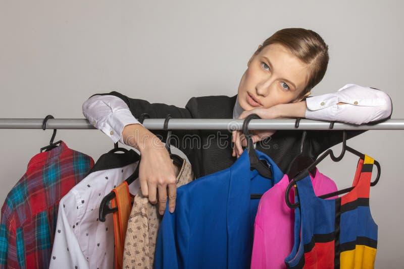 女孩站立在与衣裳和梦想的挂衣架 免版税库存图片