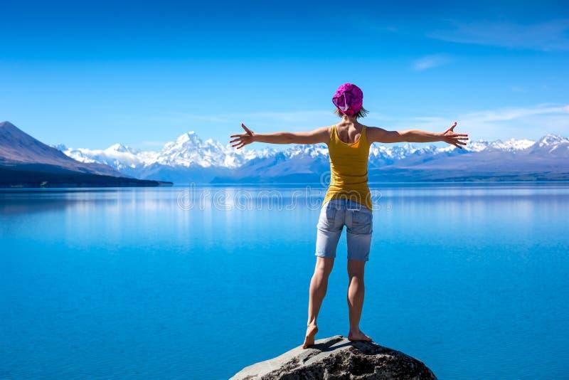 女孩站立在岩石顶部并且享受看法 免版税库存照片