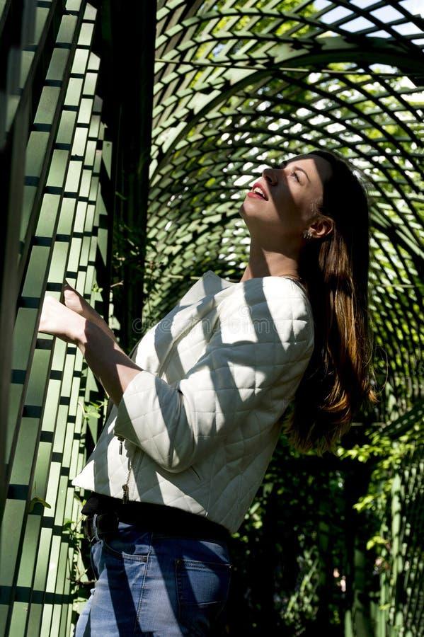女孩站立在木曲拱,曲拱秋天的阴影下  库存照片