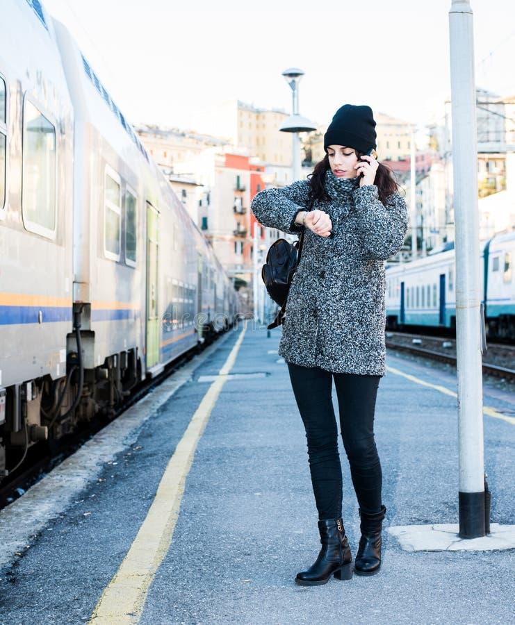 女孩站立在火车旁边,看她的手表和谈话在电话 免版税库存图片