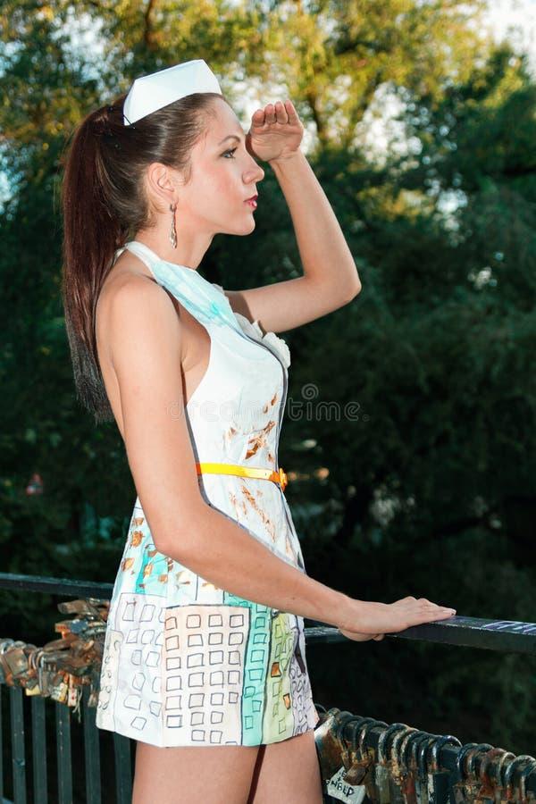 女孩站立用手到她的看在某人外面的前额一件时髦纸礼服的 免版税库存照片