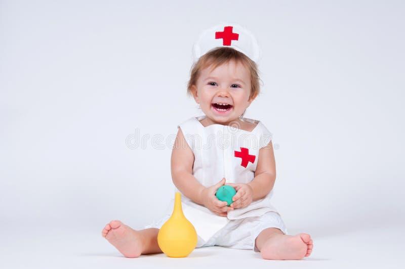 女孩笑扮演有灌肠的护士在手上 库存图片