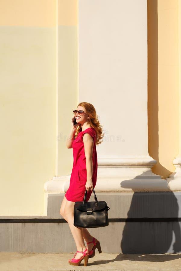 女孩红色礼服的和有一个时兴的提包的 免版税库存图片