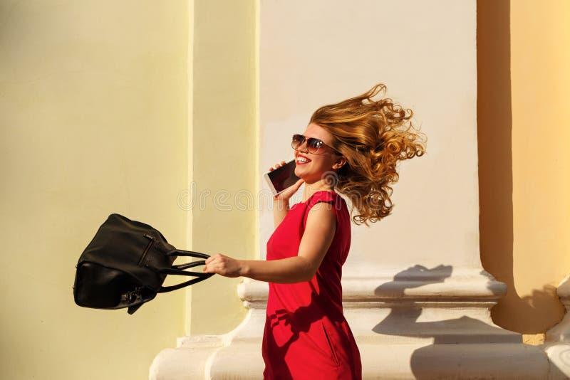 女孩红色礼服的和有时髦提包的,电话 免版税库存图片