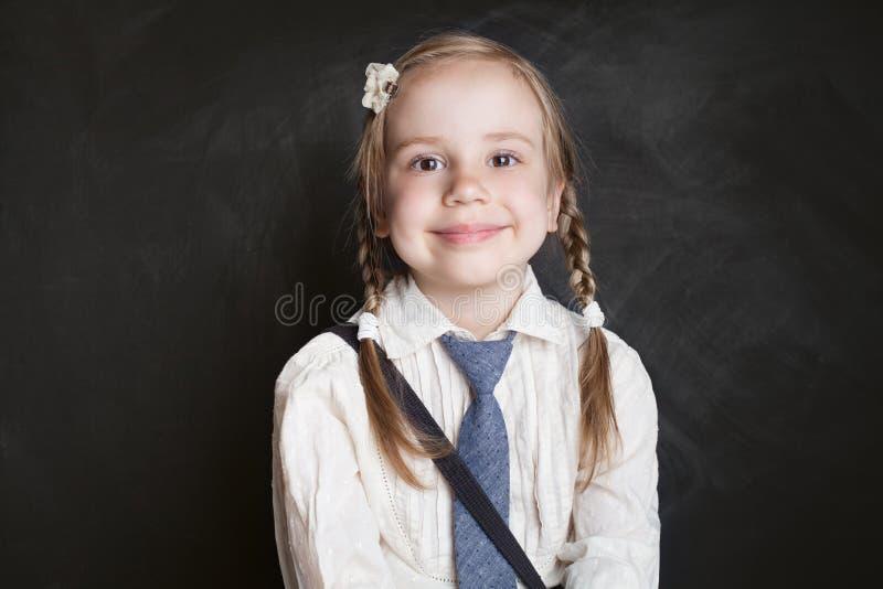 女孩纵向微笑 黑板的愉快的儿童女小学生 图库摄影