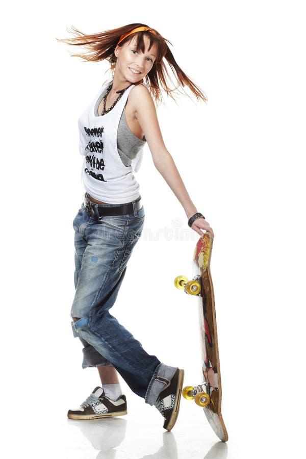 女孩纵向滑板微笑的突出 库存照片