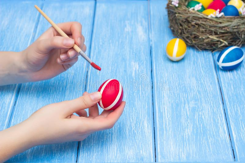 女孩绘与刷子和油漆的复活节彩蛋在说谎巢用五颜六色的鸡鸡蛋的木背景 库存图片