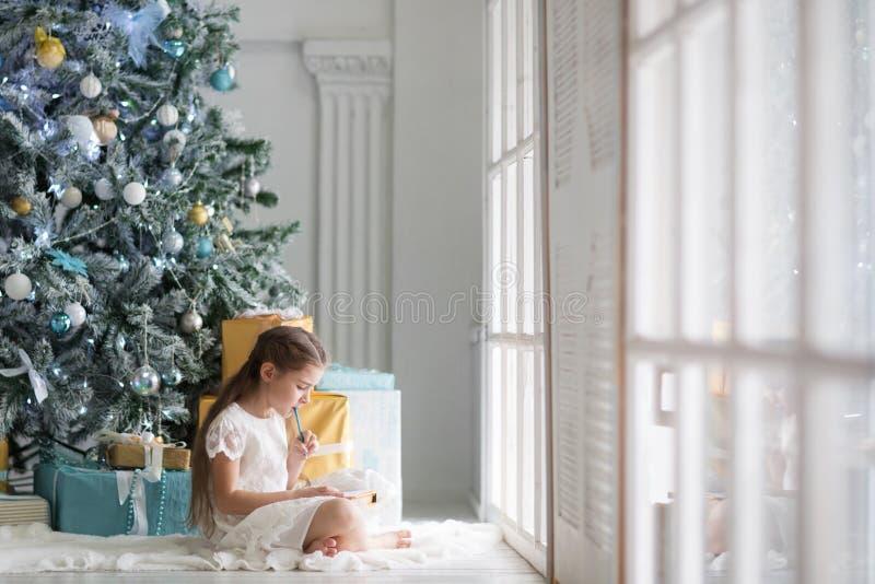 女孩给圣诞老人项目写一封信在有圣诞树的一间大和明亮的屋子在蓝色和金子颜色 图库摄影