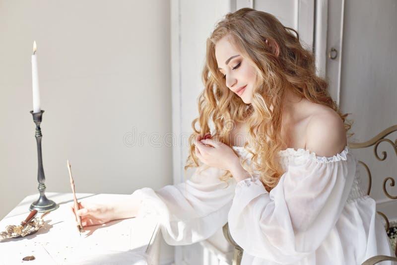 女孩给她在家坐在桌上的心爱的人写一封信在白光礼服、纯净和无罪 白肤金发卷曲 免版税库存图片
