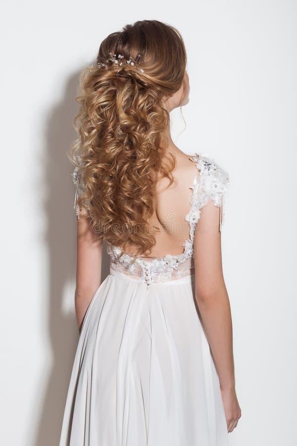 女孩美丽的精美新娘的美好的时兴的发型在白色背景的一套美丽的婚礼礼服的在Th 免版税库存照片