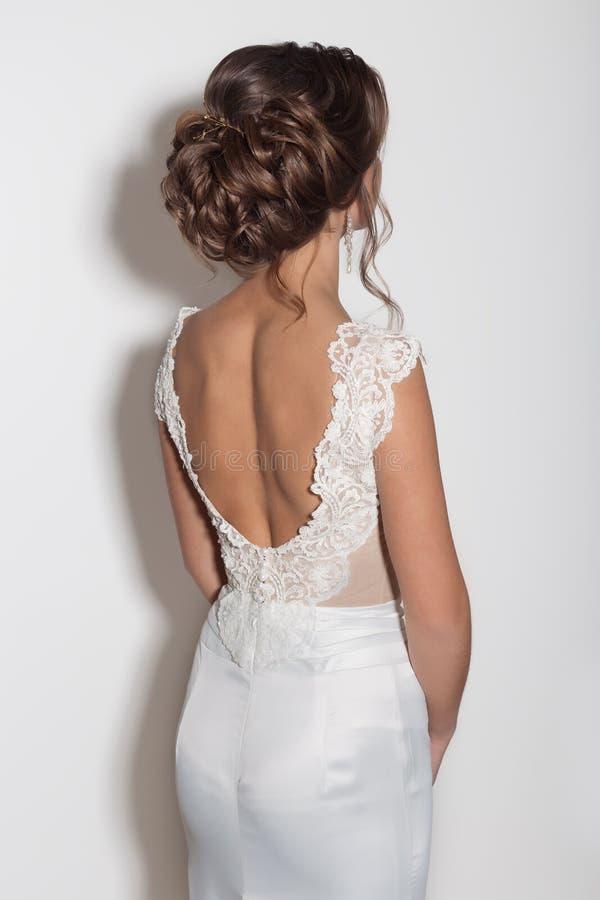 女孩美丽的精美新娘的美好的时兴的发型在白色背景的一套美丽的婚礼礼服的在Th 库存图片