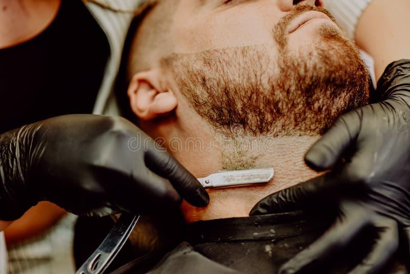 女孩美发师刮他的与人剃刀的胡子 免版税库存照片