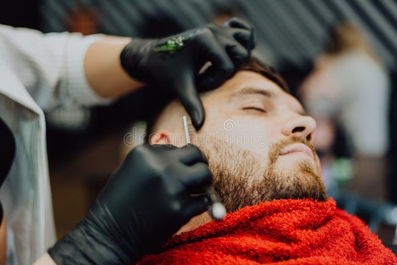 女孩美发师刮他的与人剃刀的胡子 免版税库存图片