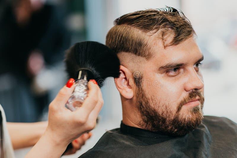 女孩美发师取消头发残滓与刷子在切开以后 免版税库存照片