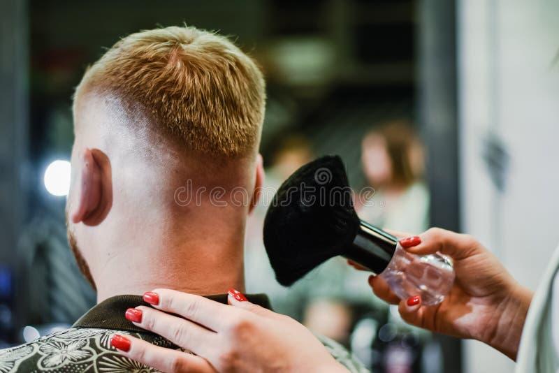 女孩美发师取消头发残滓与刷子在切开以后 图库摄影