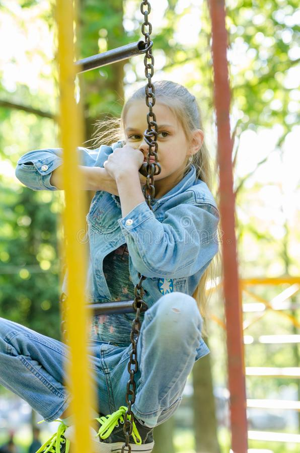 女孩考虑在操场爬了垂悬的梯子 库存图片