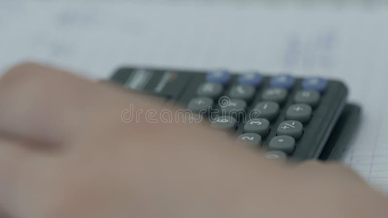 女孩考虑在计算器的检查 递妇女计算器金钱 女性办公室工作者举行安排 图库摄影