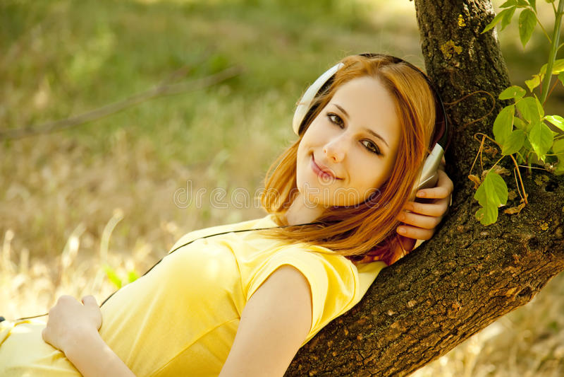 女孩耳机位于在结构树 免版税库存图片