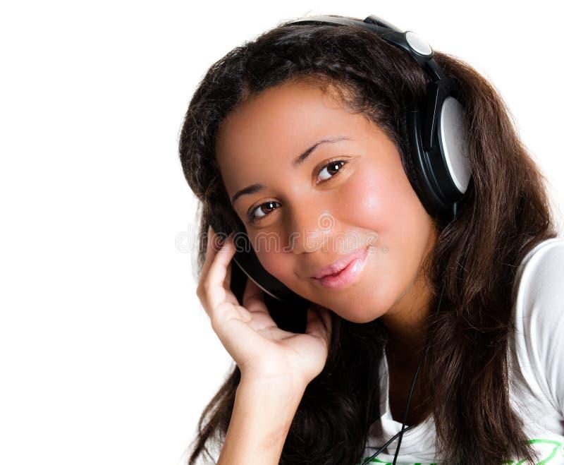 女孩耳机听的音乐少年 免版税库存照片