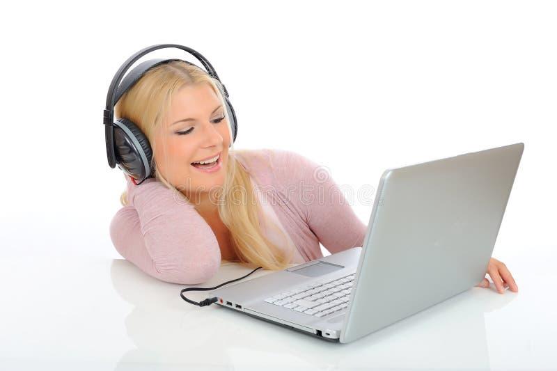 女孩耳机听的音乐相当 库存照片