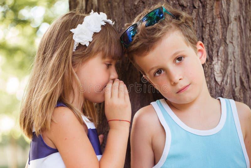 女孩耳语秘密入男孩耳朵 库存图片