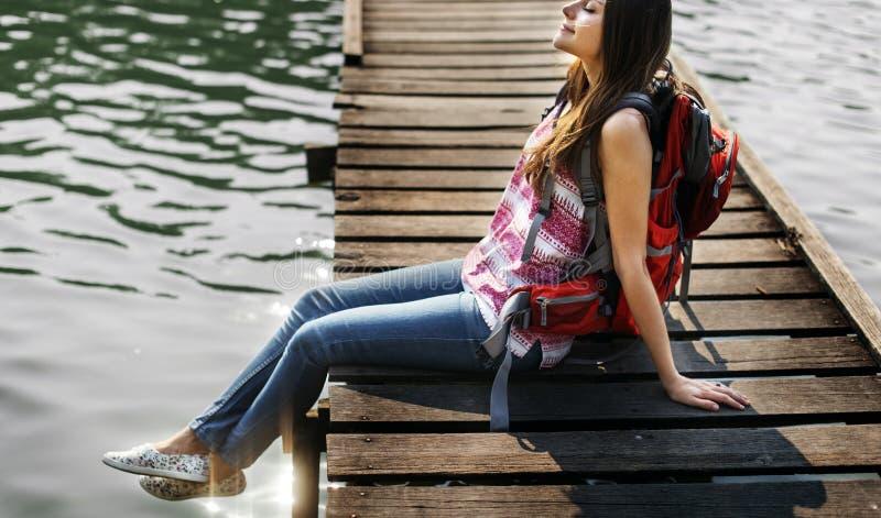 女孩背包徒步旅行者坐的ob木桥 库存照片