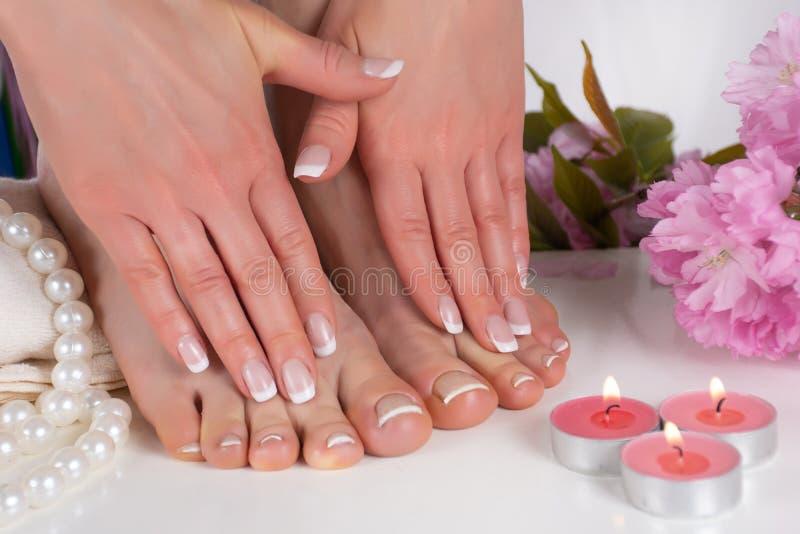 女孩脚和手有法国指甲油的在温泉沙龙与装饰桃红色花、蜡烛、珍珠和毛巾 库存照片