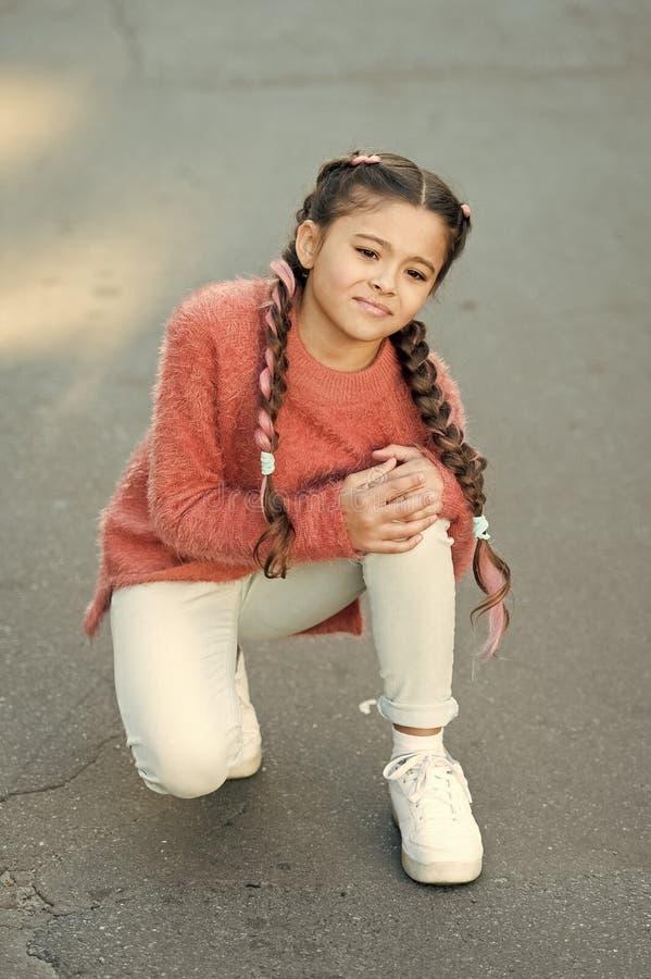 女孩腿部受伤  小孩子有痛苦在膝盖 秋天毛线衣的呼喊的女孩 秋天偎依 ?? 库存图片