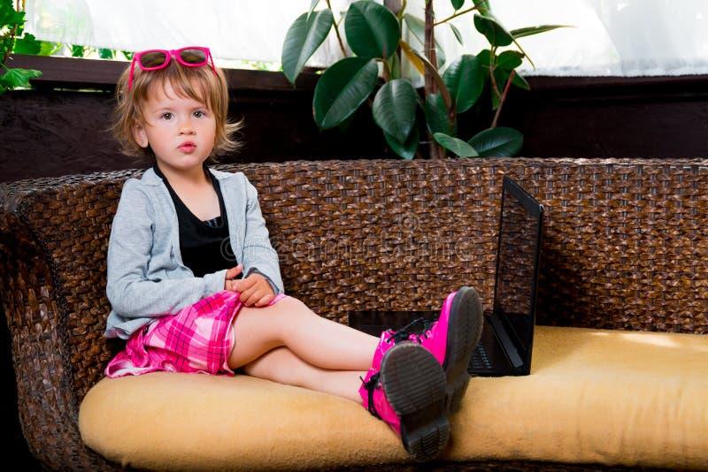 女孩膝上型计算机一点使用 桃红色裙子的孩子和起动,太阳镜,坐在沙发的灰色上面,使用 看照相机 免版税库存照片