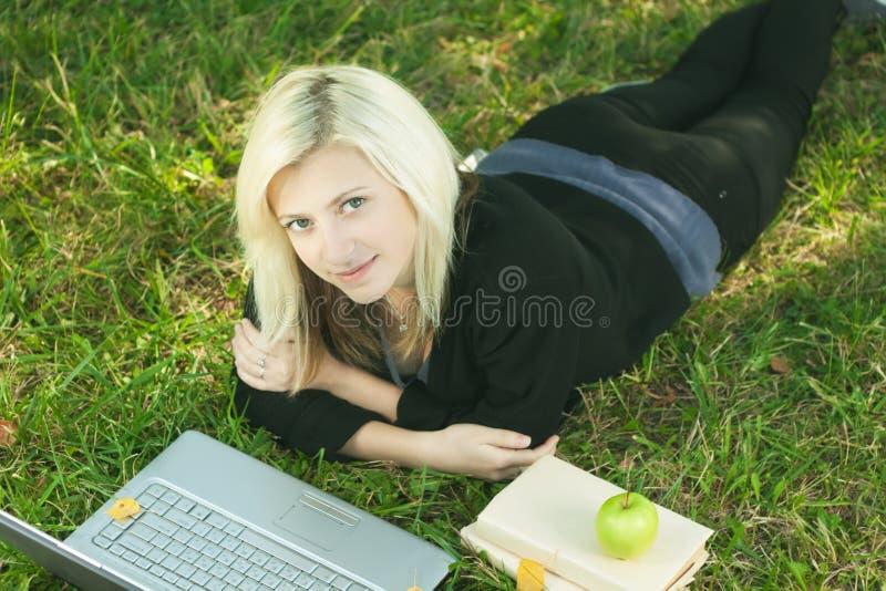 女孩膝上型计算机公园学习 免版税库存照片