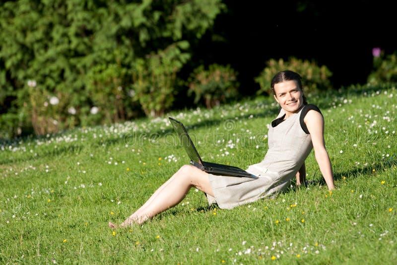 女孩膝上型计算机公园 免版税库存照片