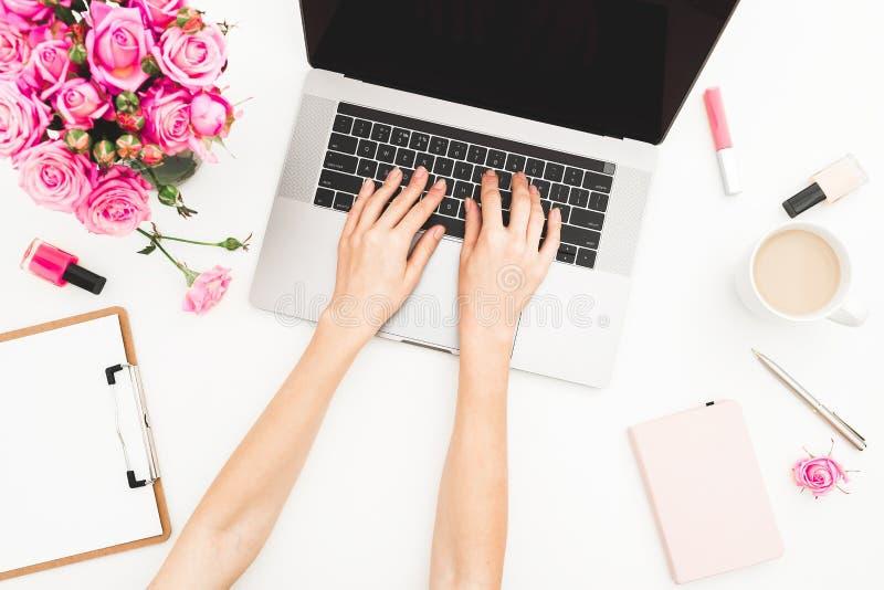 女孩膝上型计算机工作 办公室工作区用女性手,膝上型计算机,桃红色玫瑰花束,咖啡杯,在白色桌上的日志 顶视图 免版税库存图片