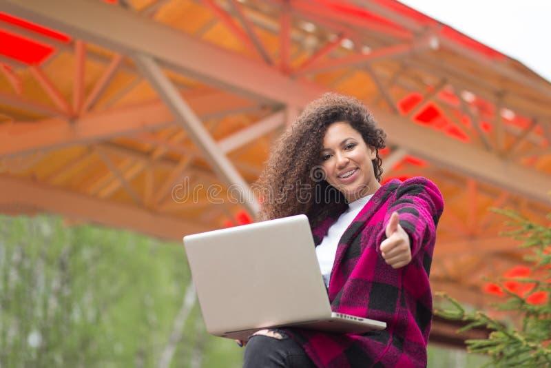 女孩膝上型计算机赞许-显示空白的黑便携式计算机屏幕的白种人妇女,看微笑的照相机,打手势 库存照片