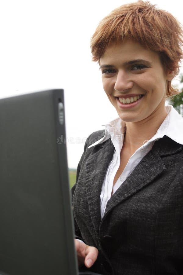 女孩膝上型计算机运作的年轻人 库存图片