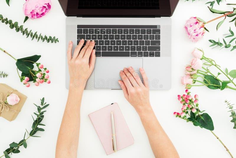 女孩膝上型计算机键入 办公室工作区用女性手、膝上型计算机、笔记本和桃红色花在白色背景 顶视图 平面 库存照片