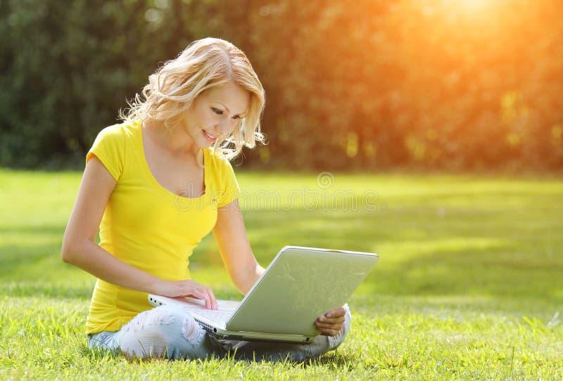 女孩膝上型计算机 有笔记本的白肤金发的美丽的少妇 库存照片