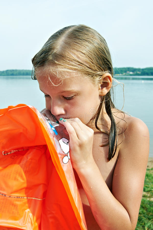 女孩膨胀在海滩的橙色床垫 免版税图库摄影