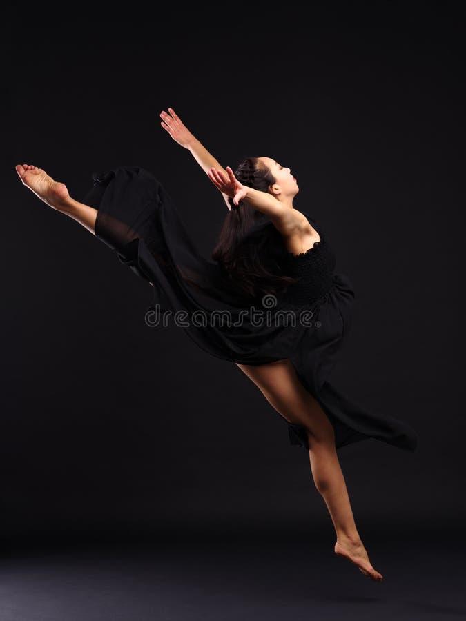 女孩舞蹈家做在麻线的一个飞跃 在黑色背景 图库摄影